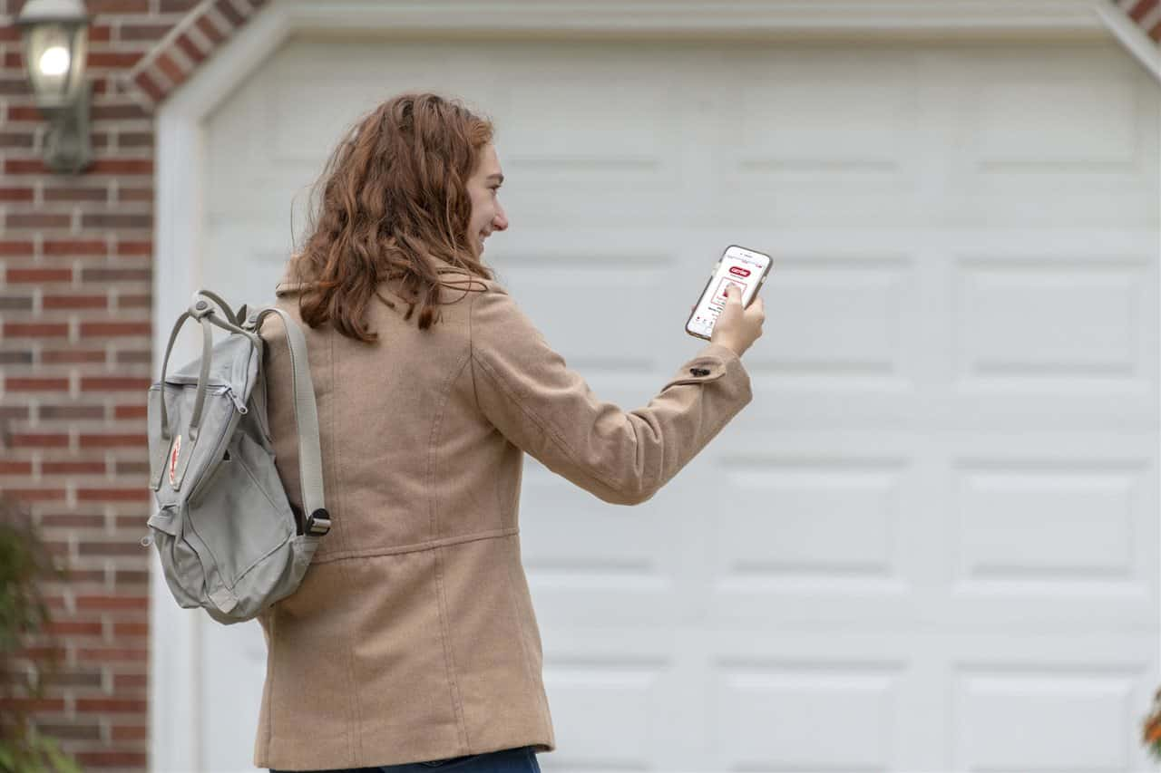 a woman looking at her phone outside the garage | Prestige Home Inspections | Connectivity Akron