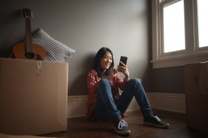 a girl sitting looking at her phone smiling | Prestige Home Inspections | moving made easy Akron