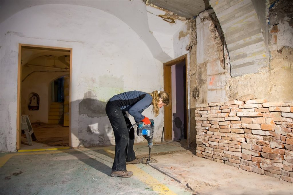 woman drilling the basement floor | Prestige Home Inspections | Bathroom in the basement Akron